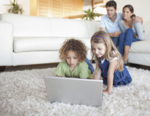 Children using a notebook while their parents are watching